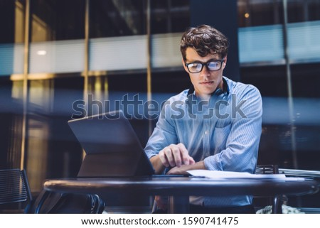 Young handsome attentive man in glasses with headphones browsing tablet sitting at table with documents at workplace. Young smart it male developer working on touch pad creating useful website