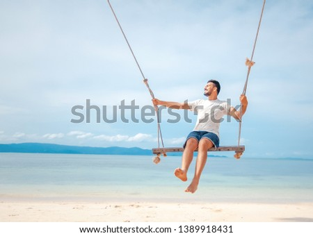 Young handsome attractive latin man rolling on a swing against the backdrop of a tropical beach and sea, vacations and travels #1389918431