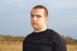 Young handsome autistic guy on a walk in the field. Brooding and lonely