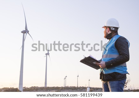 Young Handsome Beard Male Engineer in Wind Mill Power Generator Station  with white safety hat and wind turbines on background