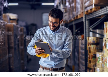 Young handsome bearded employee holding protective helmet under armpit and using tablet to check out goods.