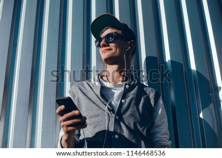 young handsome bearded hipster man using smartphone and listening music with earphones in the city, headphones, sunglasses street, outdoor portrait, cap, hat