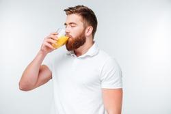 Young handsome bearded man drinking orange juice isolated on white background