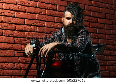 young handsome bearded man hipster or biker with long beard sitting on metallized motorbike or motor cycle on red brick wall background in garage, copy space