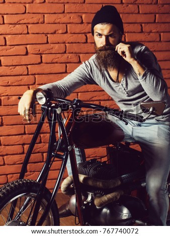 young handsome bearded man hipster or biker with long beard sitting on metallized motorbike or motor cycle with wheels on red brick wall background in garage #767740072