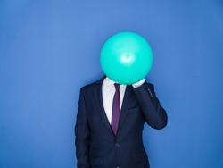 Young handsome bearded man in a suit blowing up a green balloon front view. Blue background.