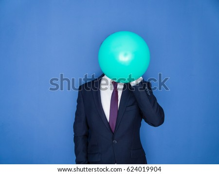 Young handsome bearded man in a suit blowing up a green balloon front view. Blue background. Сток-фото ©