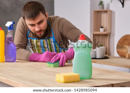 Young handsome bearded man in the kitchen, trying to clean a table using detergents, brushes, sprays #1428985094