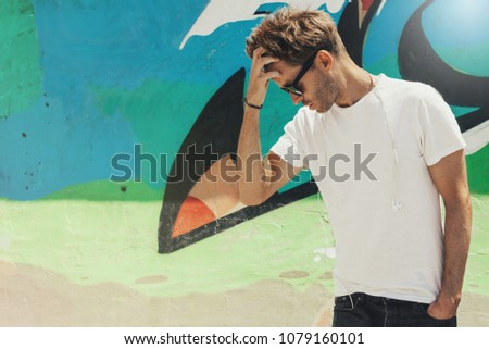 Young handsome bearded man is standing next to a colorful wall background and  wearing an empty white t-shirt and sunglasses. Horizontal mock up style. #1079160101