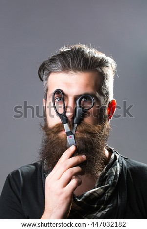 young handsome bearded man with long beard moustache and brunette hair holding hairdresser or barber scissors with emotional face in studio on grey background #447032182
