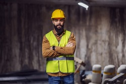 Young handsome bearded worker in vest with helmet on head standing inside of tunnel in construction process with arms crossed.