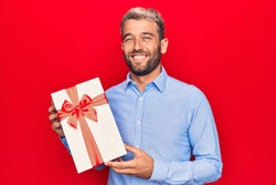 Young handsome blond man with beard holding birthday present over isolated red background looking positive and happy standing and smiling with a confident smile showing teeth