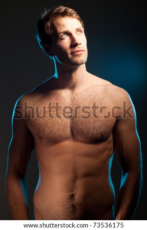Young handsome blonde man against black background