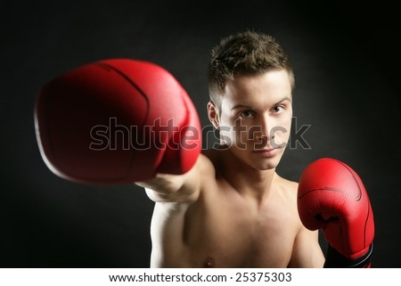Young handsome boxer man isolated on black, studio shot