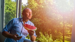 Young Handsome boy / male caucasian with closed eyes and piece of watermelon. Man with smarphone at the window . Toned vintage picture with forest. Copy space and text box. Concept of relax