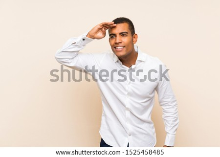 Young handsome brunette man over isolated background looking far away with hand to look something