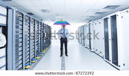 young handsome business man  engineer in  businessman hold  rainbow colored umbrella in server datacenter room  and representing security and antivirus sofware protection concept