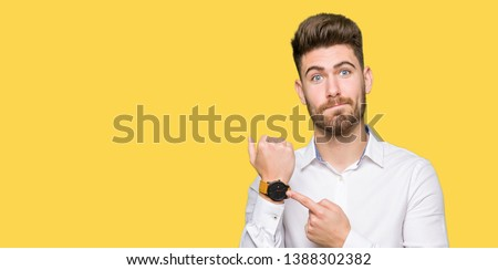 Young handsome business man In hurry pointing to watch time, impatience, upset and angry for deadline delay