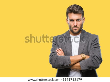 Young handsome business man over isolated background skeptic and nervous, disapproving expression on face with crossed arms. Negative person.