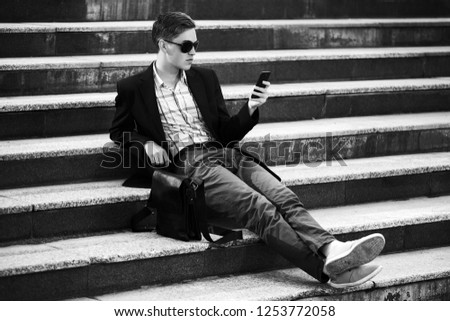 Young handsome business man using cell phone sitting on steps Stylish male model wearing black jacket and gray pants