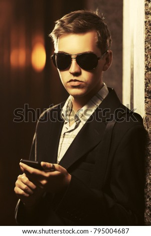 Young handsome business man using smartphone in a night city street. Stylish fashion male model in black blazer outdoor
