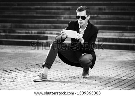Young handsome business man using tablet computer on city street Stylish trendy male model wearing sunglasses and black suit jacket