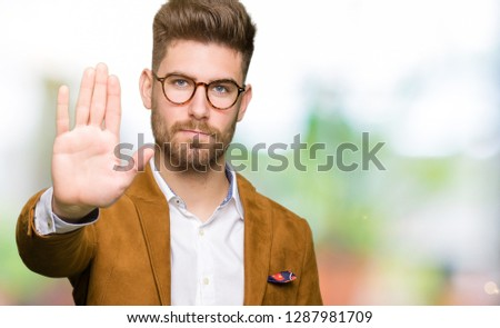 Young handsome business man wearing glasses doing stop sing with palm of the hand. Warning expression with negative and serious gesture on the face. #1287981709