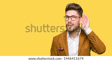 Young handsome business man wearing glasses smiling with hand over ear listening an hearing to rumor or gossip. Deafness concept.