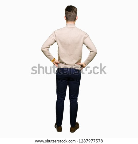 Young handsome business man wearing glasses standing backwards looking away with arms on body
