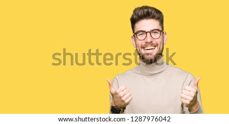 Young handsome business man wearing glasses success sign doing positive gesture with hand, thumbs up smiling and happy. Looking at the camera with cheerful expression, winner gesture. #1287976042