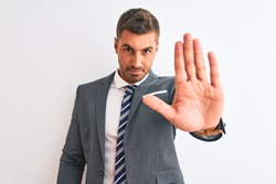 Young handsome business man wearing suit and tie over isolated background doing stop sing with palm of the hand. Warning expression with negative and serious gesture on the face.