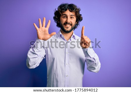 Young handsome business man with beard wearing shirt standing over purple background showing and pointing up with fingers number six while smiling confident and happy. Foto stock ©