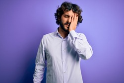 Young handsome business man with beard wearing shirt standing over purple background Yawning tired covering half face, eye and mouth with hand. Face hurts in pain.