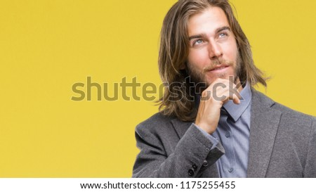 Young handsome business man with long hair over isolated background with hand on chin thinking about question, pensive expression. Smiling with thoughtful face. Doubt concept.