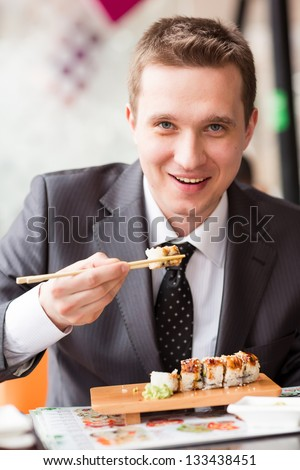 Young handsome businessman eating sushi with sticks in a cafe