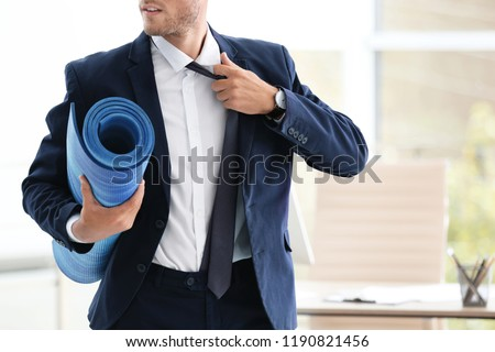 Young handsome businessman holding yoga mat in office. Gym after work #1190821456