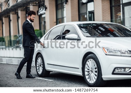 Young handsome businessman in black suit enters the rear seat of his car near a modern business center, on the street. #1487269754