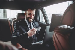 Young handsome businessman is sitting in luxury car. Serious bearded man in suit is working with laptop with credit card in hands.
