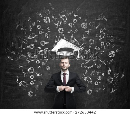 Young handsome businessman is thinking about education at business school. Drawn business icons over the dark concrete wall. Graduation hat.