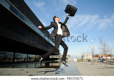 Young handsome businessman jumping in the street