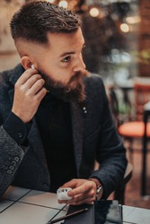 Young handsome businessman putting airpods in his ears while working in a cafe and preparing for a conference call with his colleagues