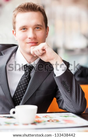 Young handsome businessman sitting in a cafe drinking coffee