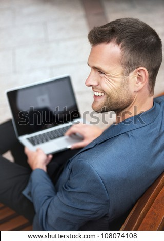 Young handsome businessman sitting on a wooden bench in the city with a laptop and smiling. From above