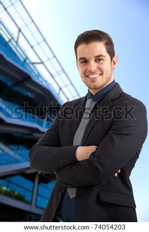 Young handsome businessman smiling. Blue blurred background.