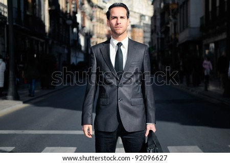 Young handsome businessman standing in the street