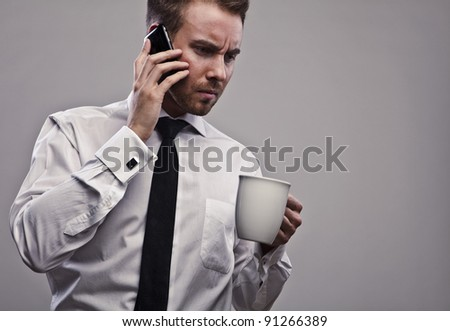 Young handsome businessman talking on mobile phone.