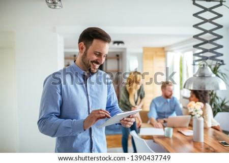 Young handsome businessman using digital tablet