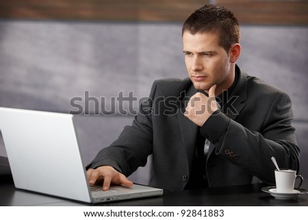 Young handsome businessman using laptop in elegant office.?
