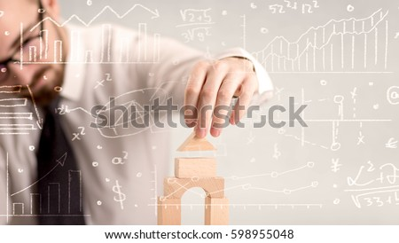 Young handsome businessman using wooden building blocks with white calculations scribbled around him #598955048