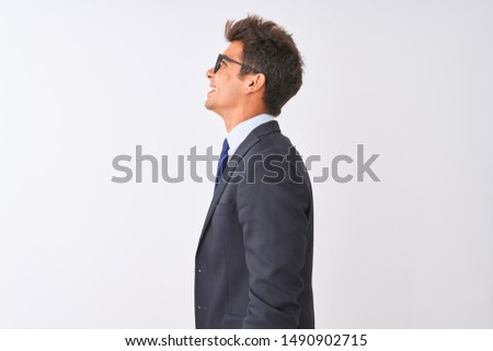 Young handsome businessman wearing suit and glasses over isolated white background looking to side, relax profile pose with natural face with confident smile.